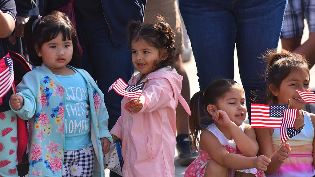 A group of young girls enjoyed waving their American flags as units passed by.
