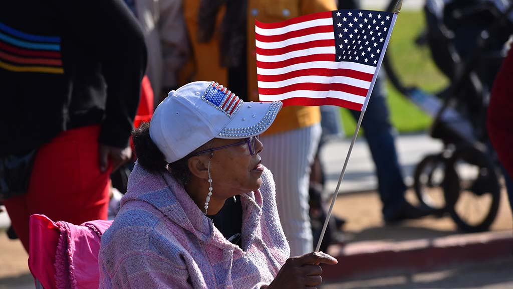 Marilyn Wells of Escondido, whose parents were veterans, watched the parade contingents. Photo by Chris Stone