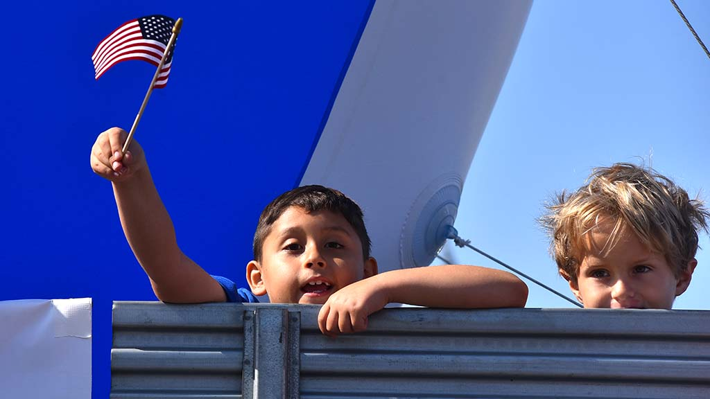 "A boy holding a flag while riding on a Chase Bank float shouts ""USA"" down the parade route."