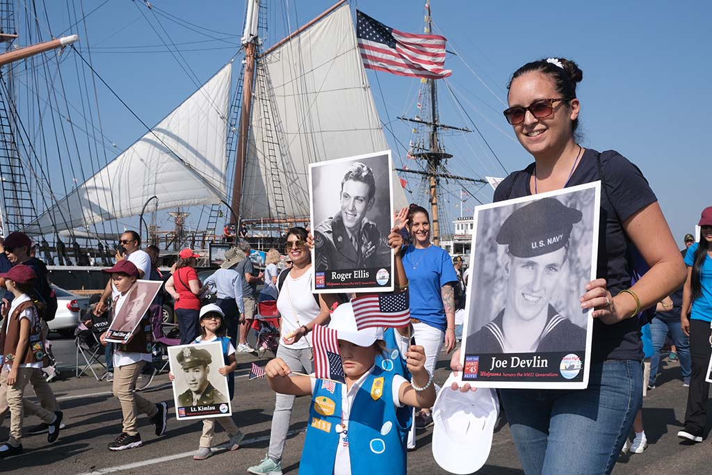 Girl Scouts and leaders carry photos of fallen World War II veterans.