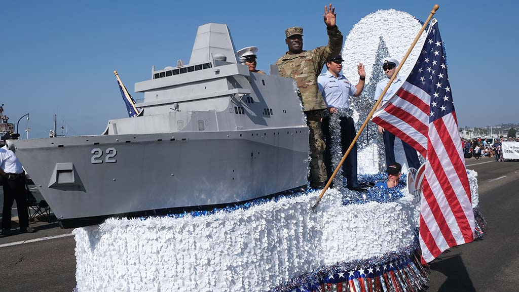 Military members ride on a float celebrating a new littoral ship, the USS San Diego.
