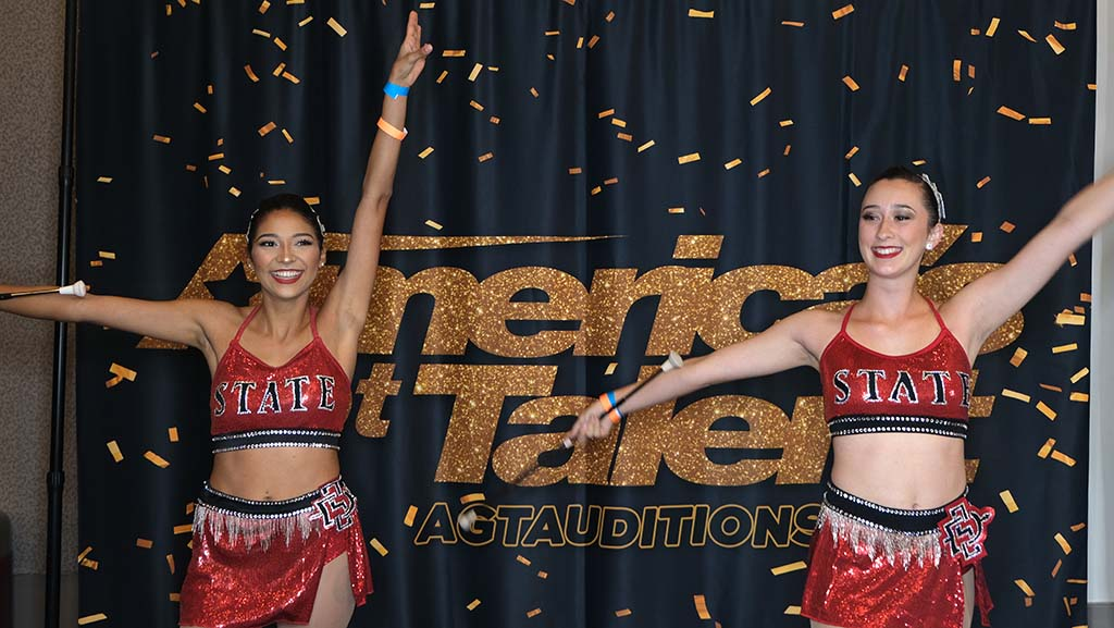 San Diego State marching band baton twirlers Alexis Gallegos (left) and Kari Webb shared act before selfie backdrop in holding room