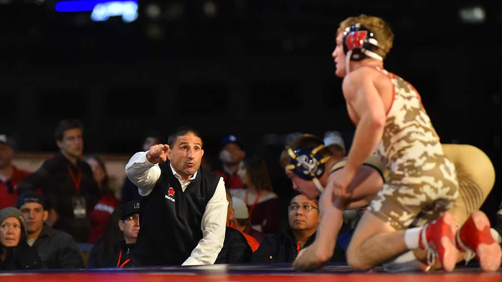 Wisconsin head coach Chris Bono shouts instructions to Tyler Dow in 184-pound match with Navy's Andrew Buckley. Dow won in overtime.