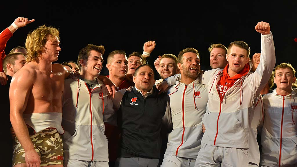 Wisconsin wrestlers celebrate win with their coach after defeating Navy 24-12 in opening match of season.