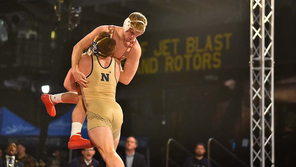 Navy's Tyler Dow lifts Wisconsin's Andrew Buckley in 184-pound match.