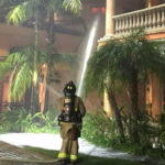 Firefighter sprays water on the burning home