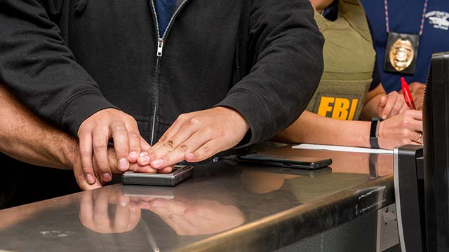 Suspect is fingerprinted during South Bay raids