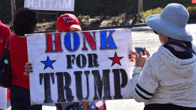 A few dozen supporters of President Trump line Avenida Del Oro in Oceanside to protest an appearance by Speaker Nancy Pelosi.