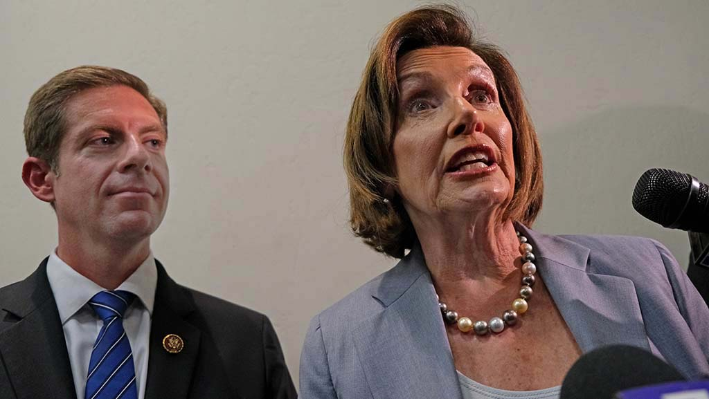 Rep. Mike Levin stood beside House Speaker Nancy Pelosi, guarded by Secret Service members, as she spoke to local news outlets after her appearance.