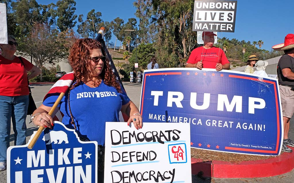 A member of Indivisible and a President Trump supporter vie for drivers' attentions in Oceanside where Speaker Nancy Pelosi appeared.