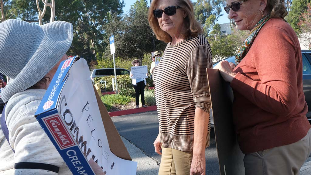 Two Democratic supporters (right) exchange comments with a President Trump supporter bearing a sign calling Nancy Pelosi a communist