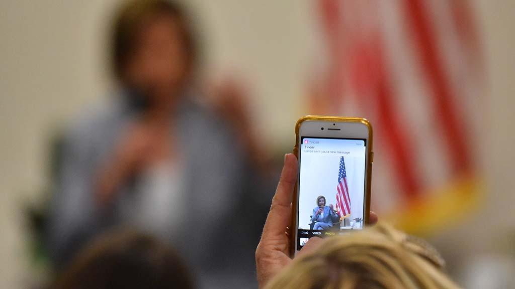 An audience member records the Oceanside appearance of Speaker Nancy Pelosi.