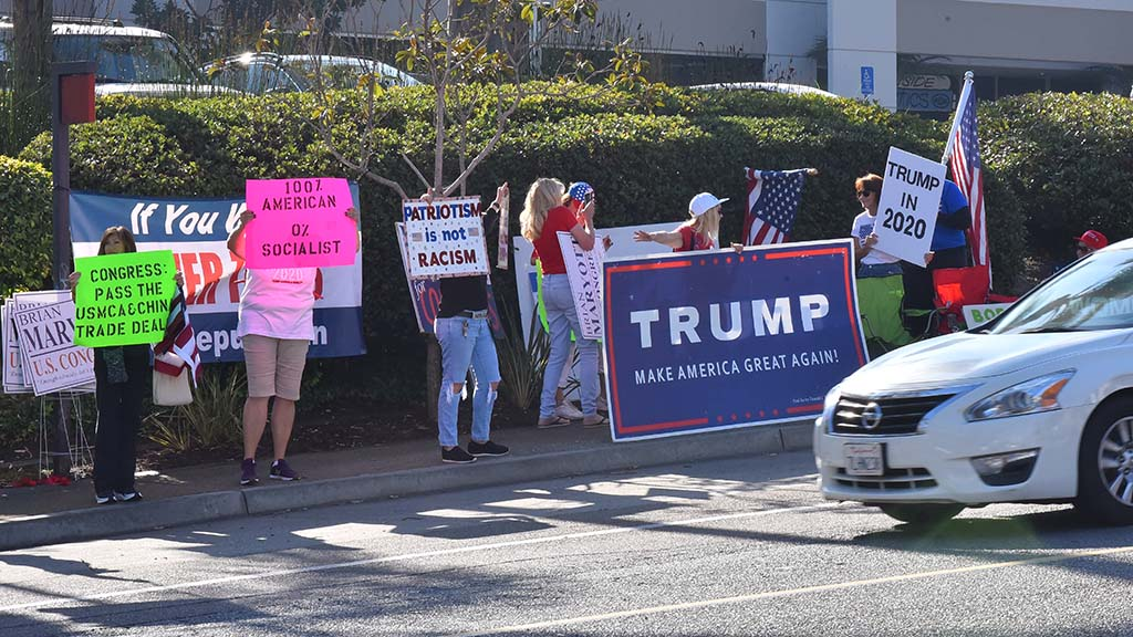 Supporters of President Trump stand along Avenida Del Oro in Oceanside to protest appearance of Nancy Pelosi.