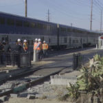 San Diego Sheriff's Department investigators gather next to the train