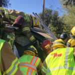Cal Fire personnel work to free trapped minivan occupants