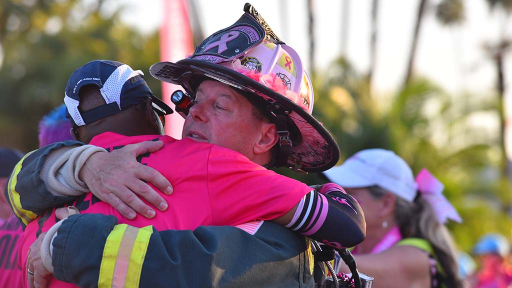Retired fireman Dale Emmerich gets a hug from San Diego Police Sgt. Vernon Peterson near the finish line of the breast cancer walk.