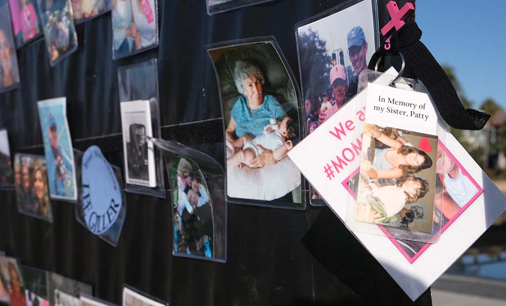 A memorial wall displays photos of victims of breast cancer at the Susan G. Komen 3-Day Walk closing ceremonies at Waterfront Park.