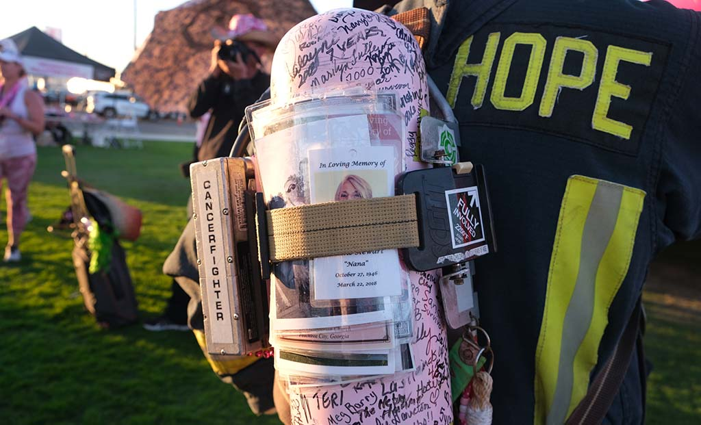Retired fireman Dale Emmerich of Dane County, Wisconsin carries an air tank with names of breast cancer survivors.