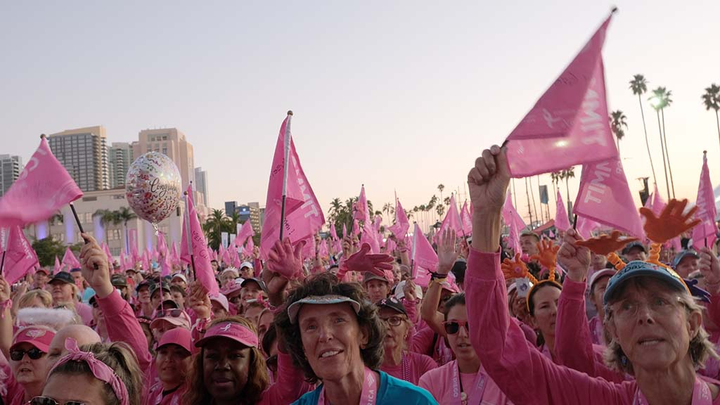 Breast cancer survivors raise their flags and cheer as the Susan Komen 3-Day Walk comes to an end.
