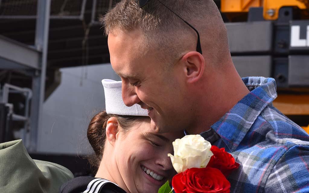 Sgt. Tyler Schott greets his wife, Ariel, a petty officer 3rd class on the USS Boxer.