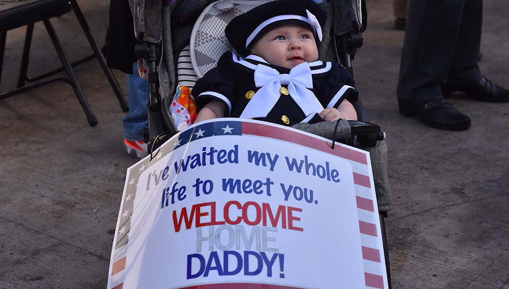 Five-month-old Evelynn Doyle gets ready to greet her father, Adam Doyle, a Aviation Boatswain's Mate, Handling