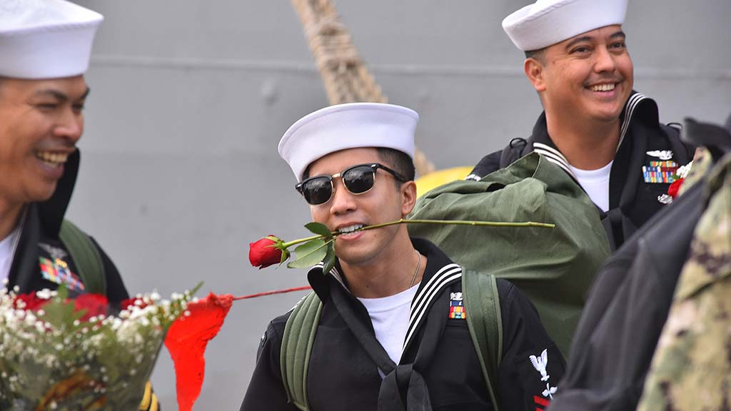 A sailor departs the USS Boxer with a rose while his hands were occupied.