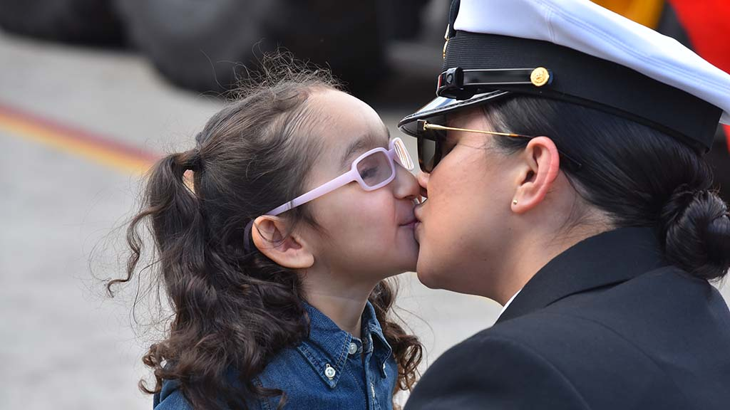 Evelina Flores, 4, gives her mother, Brenda, a welcome home kiss at Naval Base San Diego.