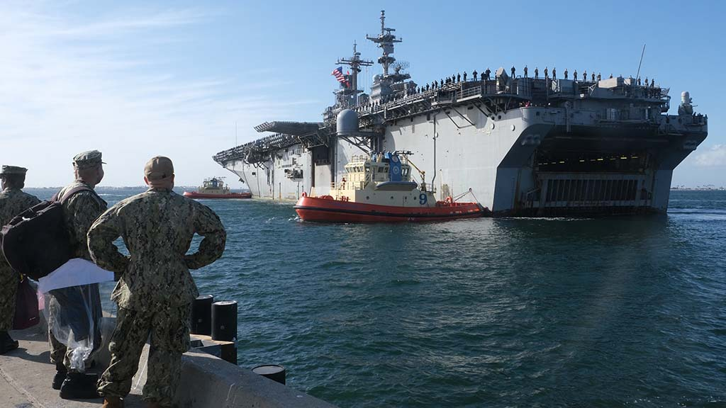 Tug boats help maneuver the USS Boxer into its port at Naval Base San Diego after a seven-month deployment.