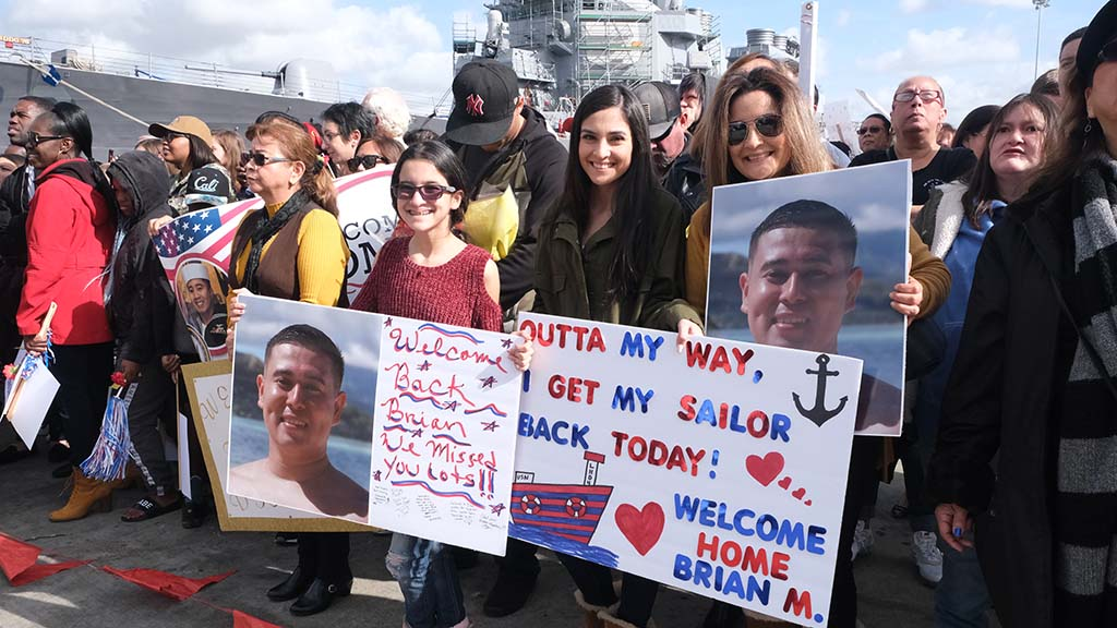 Hundreds of family and friends wait at a pier on Naval Base San Diego to greet their loved ones returning from deployment.