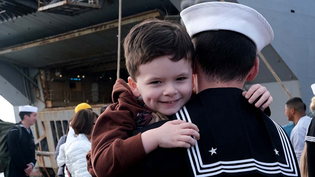 George Cavell's face tells it all in the arms of his returning dad, Jonathan.