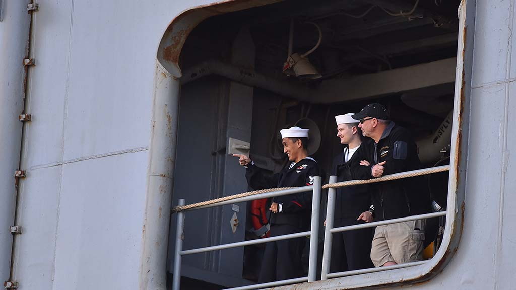 A sailor points to a crowd of waiting family and friends as he awaits returning to terra firma.