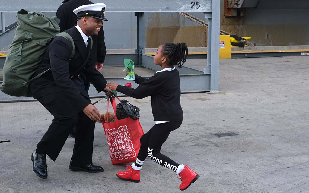 Navy officer Braswell Demontray is greeted by his daughter Azareea at Naval Base San Diego.