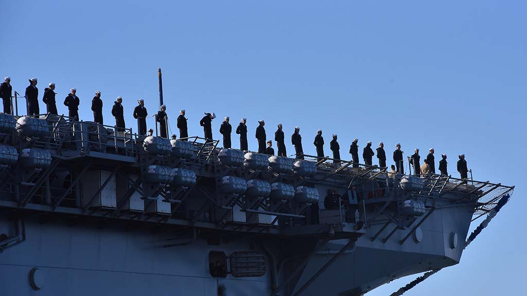 Naval and Marine personnel are lined up as they await their arrival at Naval Base San Diego.