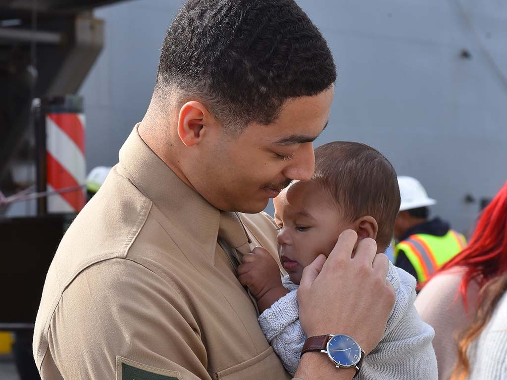 """Marine Cpl. Avery Tyler Griham meets his five-month-old son, Aries, who he called """"little me."""""""