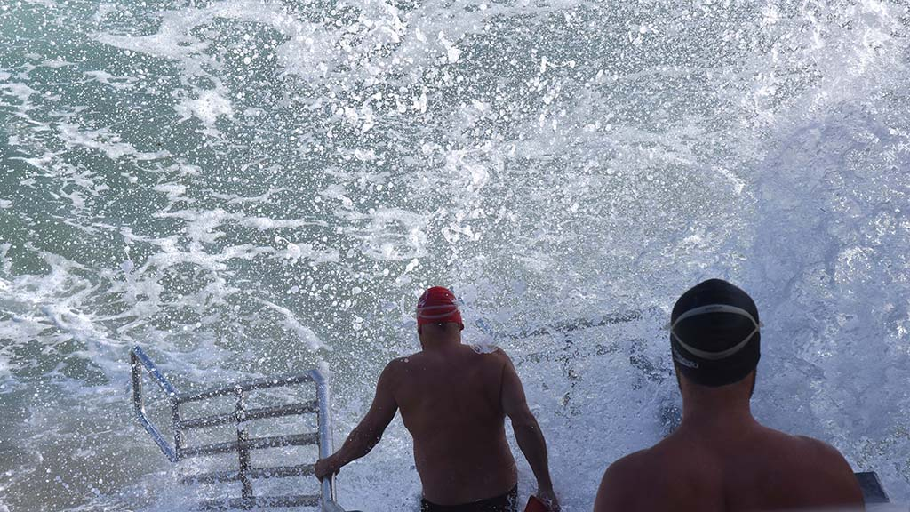 Swimmers at La Jolla Cove are greeted by waves crashing into the stairway to the beach.