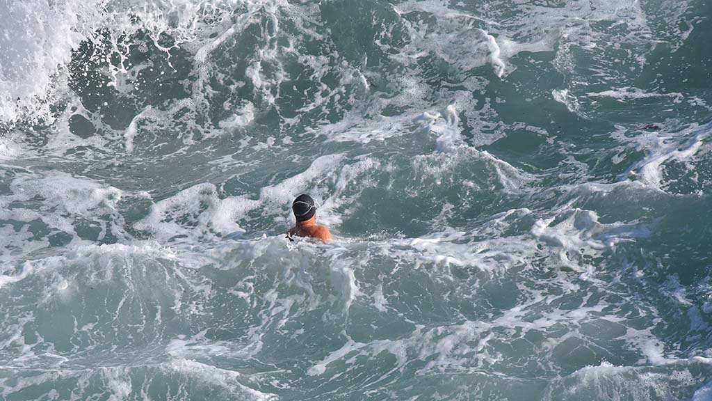 A swimmer braves a churning sea as king tide waves crash into La Jolla Cove.