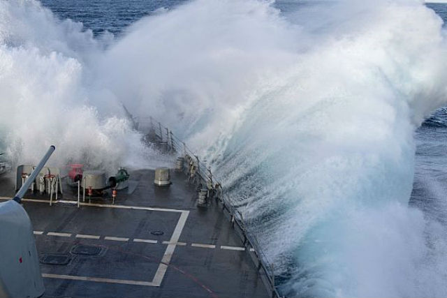 Waves break over bow of USS Paul Hamilton