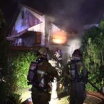 Firefighters outside the burning residence