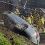 Crews examine car that ended up on its side after crashing fence.