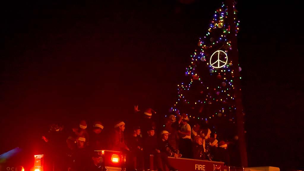 Children on a fire vehicle pass the lighted Ocean Beach tree.