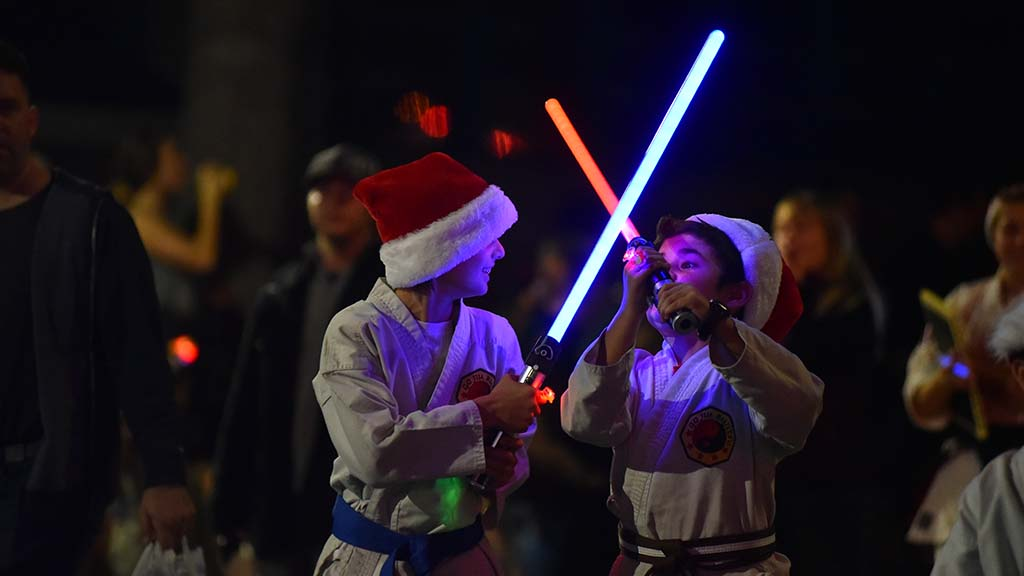 Boys in a martial arts group battle with light sabers as they make their way down the parade route.