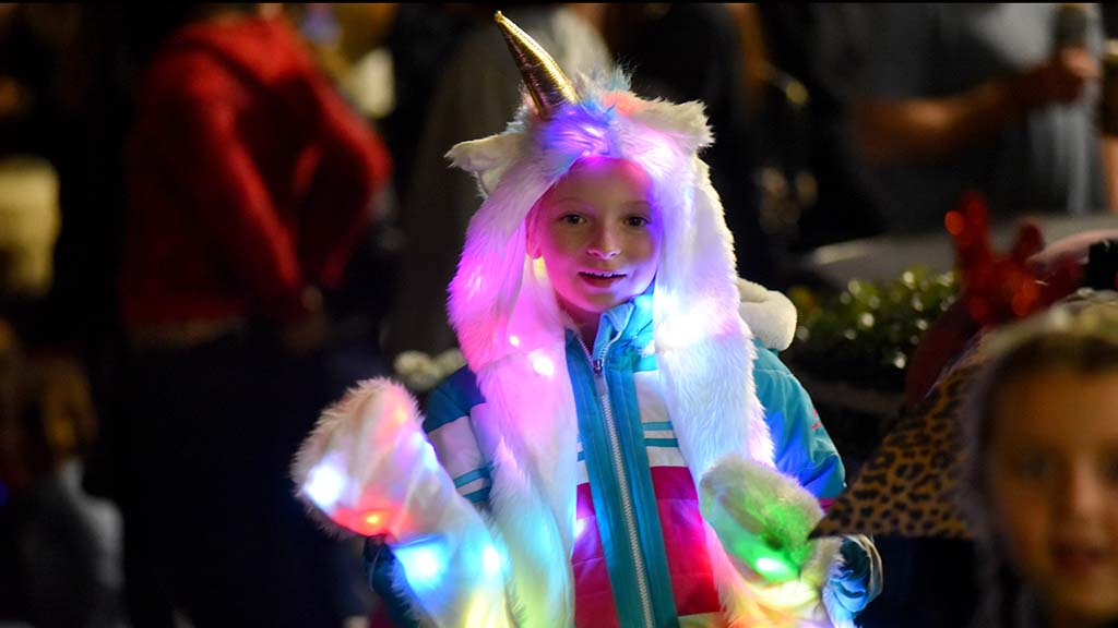 A girl dressed as a unicorn waves as parade participants pass.