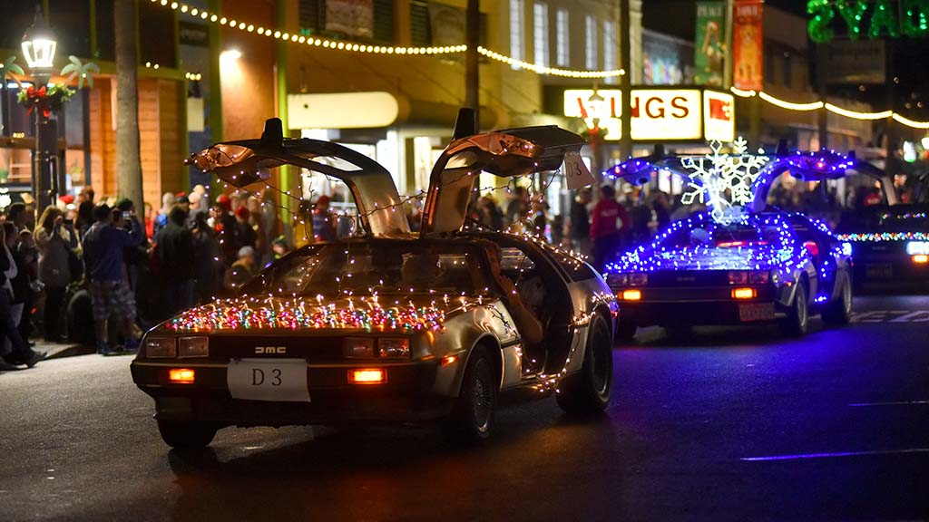 Holiday-decorated Deloreans excite thousands of spectators along Newport Avenue in Ocean Beach.
