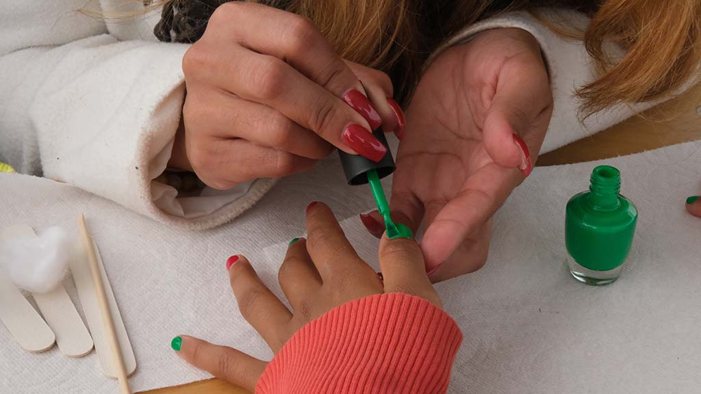 A little girl receives holiday inspired nail polish thanks to a volunteer.