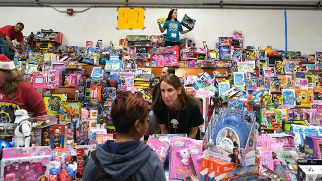 A volunteer asks a boy what toy he would like as he faces a mountain of free toys.