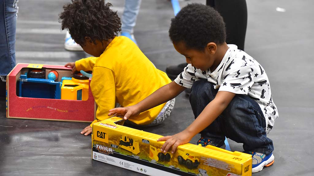 Two children couldn't wait to get out the doors before playing with their toys.