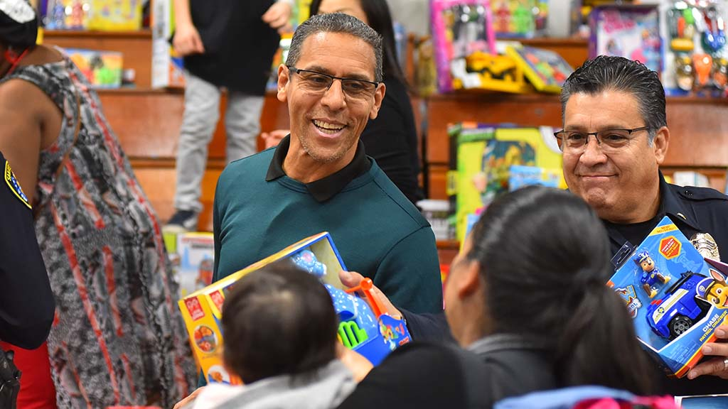Pastor Miles McPherson of Rock Church (center) asks a mother what toy she wanted for her baby.