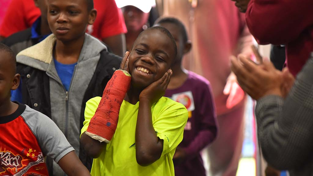 A boy is overjoyed as he walks into the high school gym filled with free toys at Toys for Joy.