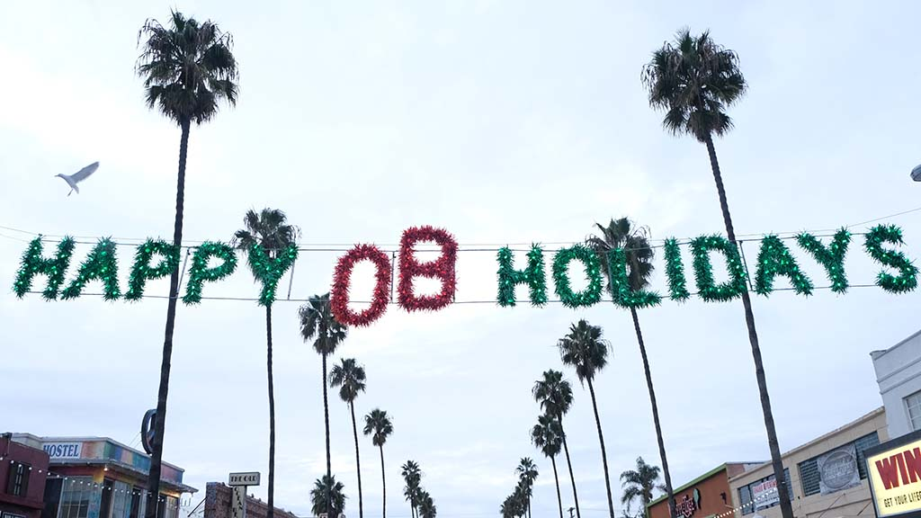 A dovelike bird flies past the traditional Happy OB Holidays sign on Newport Avenue.