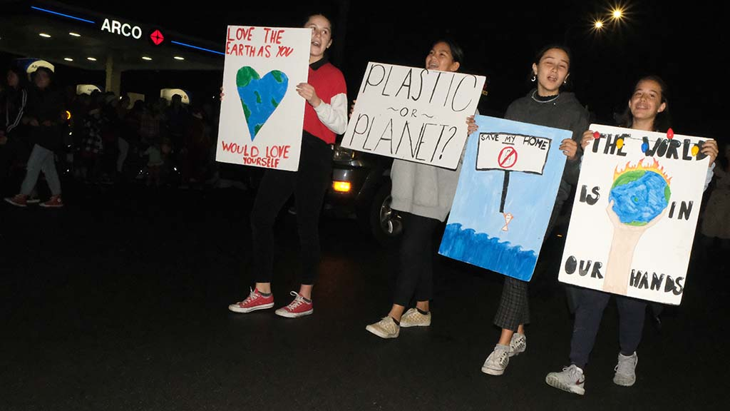 Young people holding signs for planet protection march past the ARCO station on Newport Avenue.